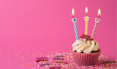 cupcake with three candles on pink background